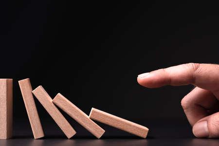 Closeup hand push the wooden domino fall down