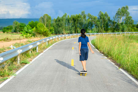 Child girl playing skateboard on the asphalt road in countryside