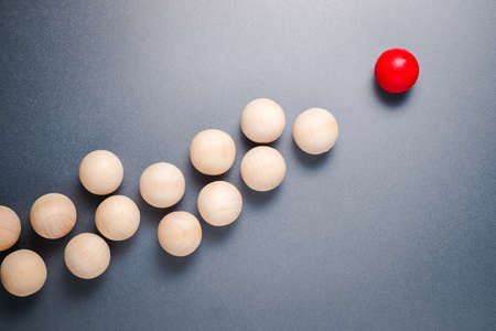 Different wooden red ball in higher position and lead the group of original wood balls