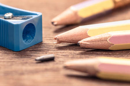 Closeup blunt pencils need shaving with old sharpener on wood table, learning and writing concept