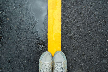 Closeup feet in sneakers standing between the yellow line of wet asphalt road after rain, make a dicision to stop or step forward, left or right 写真素材