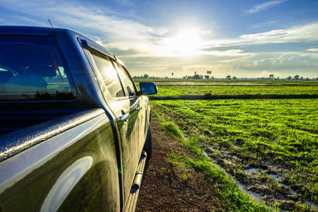Part of pickup truck on the dirt road at the rice field before sunset, travel along the countryside