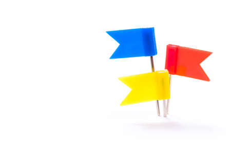 Different color flag push pins prick together at one point, isolated on white background