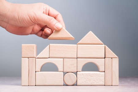 Closeup hand build a house by geometry wood toy, creative idea, dream house and architecture concept