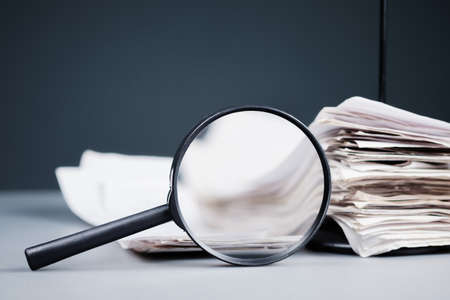 Magnifying glass with stack of receipts in paper nail on the desk, inspect income, sale analysis concept
