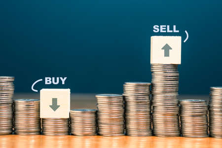 Heap of coins with wood block sign of Buy and Sell at the low and high position, Sell high Buy low in stock market concept