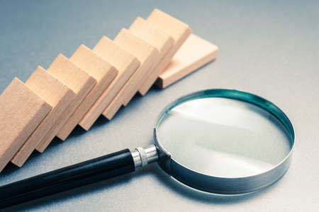 Magnifying glass and a row of fallen domino on gray background, domino effect analysis concept 写真素材