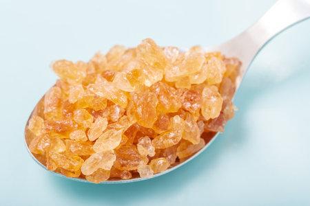 Closeup pile of rock sugar on tablespoon, spoon of crystal sugar on ceramic dish