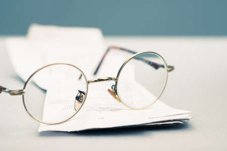 Closeup eyeglasses on some recipts on the table, check the living daily expenditure, personal finance, or tax payment concept