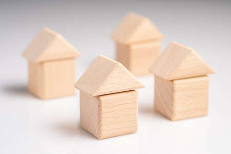 Geometry wood blocks arranged as a group of houses on white background, housing development, real estate concept 写真素材
