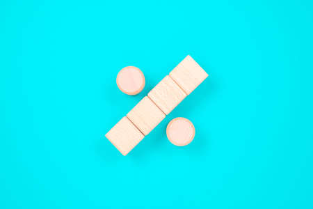 Percentage sign arranged by wood blocks on turquoise color paper background