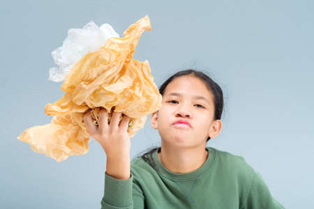 Eleven years old girl show the crumpled grocery plastic bags, remind to reduce plastic bags, focus at her hand 写真素材