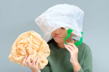 Eleven years old girl with plastic bag over her head, plastic bags reduction concept