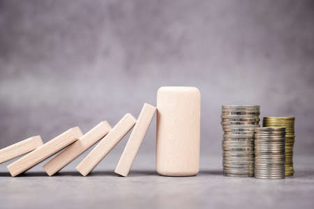 Thick wood block protect the heap of money from the effect of domino, crisis management, solution to support business and economic 写真素材