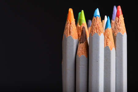 Closeup bunch of color pencils in used and old condition on black background, usable pencils to start a creative work 写真素材