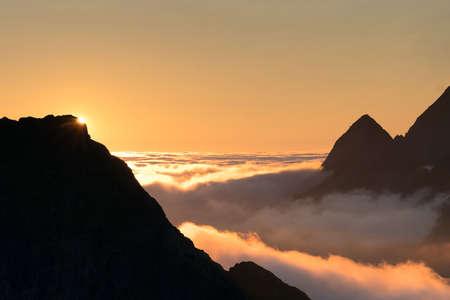 レーヌ、ロフォーテン諸島、ノルウェーにトップの山で曇り夕焼け空
