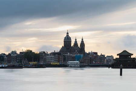 日没後にすぐに港と聖ニコラス大聖堂で長い露光スカイライン, アムステルダム, オランダ