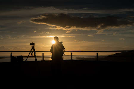Silhouette of a photographer who  stand at sunset in Alesund at sunset in summer, Norway Stock Photo