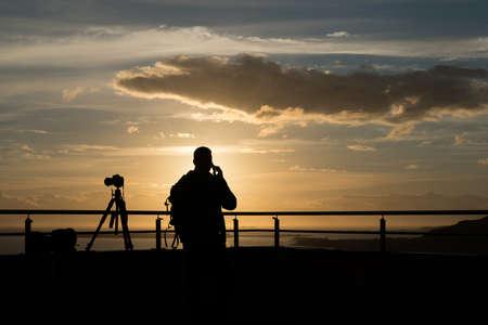 オーレスンでの夏、ノルウェーの夕日夕日に立つカメラマンのシルエット