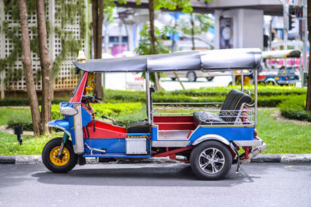 A three wheeled tuk tuk taxi on a street in the Thai capital photo