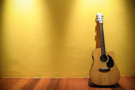 acoustic guitar  leaning on yellow wall photo