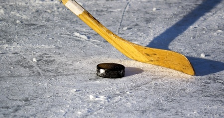 hockey stick and puck on the ice photo