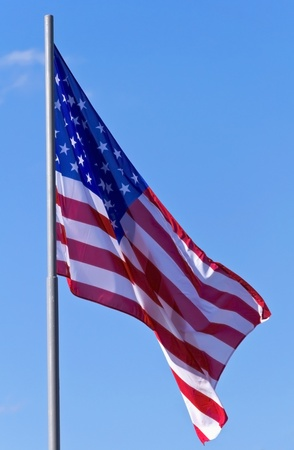 flagpoles: U S  flag on a background of blue sky