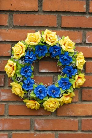 Blue yellow memory wreath on old wall Banco de Imagens