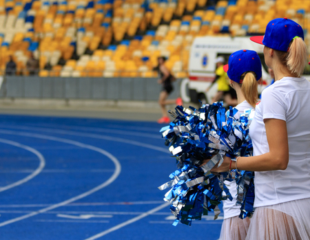 girls cheerleaders in the stadium with pompoms. Stock Photo
