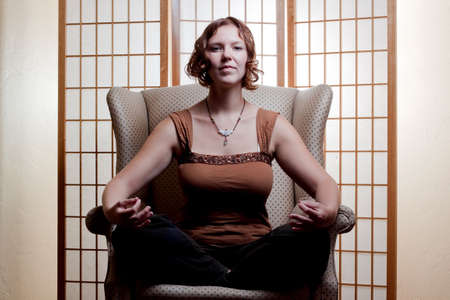 A beautiful young woman meditates in a chair Stock fotó