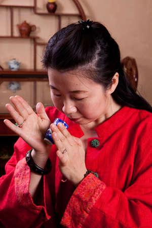 tea house: Attractive woman inside a traditional tea house, reading tea leaves