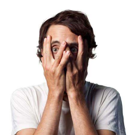 Terrified young man hides his face Stock Photo