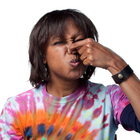 nose: Woman holds her nose for a bad smell Stock Photo
