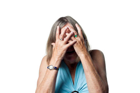 oap: Senior woman hides behind her hands, scared of something unseen