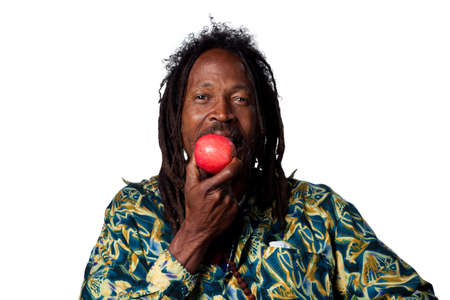 Rasta man eating an organic apple, studio shot