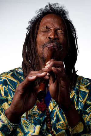 Man plays a traditional wooden flute, studio image