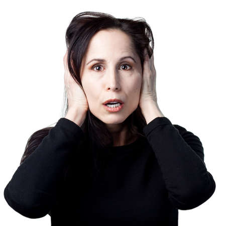 loud: Woman covers her ears after a loud noise Stock Photo