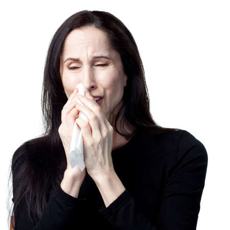 Woman with allergies using a tissue, isolated image photo