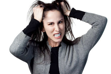 angry woman: Woman pulling out her hair in frustration, isolated image