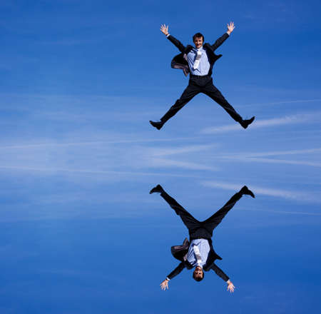 Reflection of a businessman jumping against blue skies photo