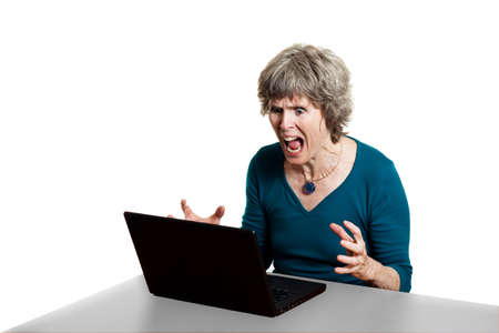 woman screaming: Attractive older lady with laptop problems, shouting at her PC Stock Photo