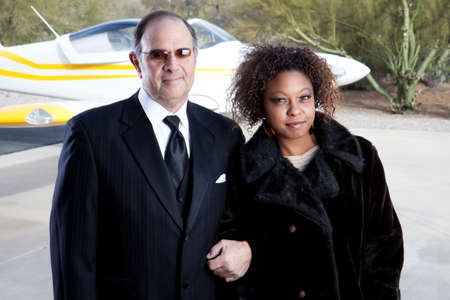 wealthy interracial couple and private plane photo