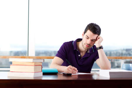 Young man relaxing and writing in the library Stock Photo - 12039814