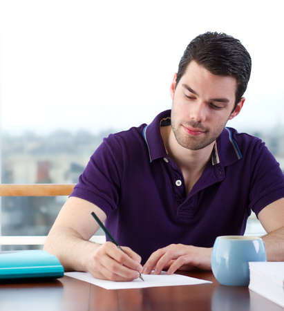 Attractive young man writes a letter by hand photo