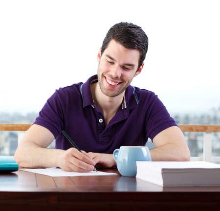 hombre escribiendo: Hombre joven feliz escribiendo una carta a mano Foto de archivo