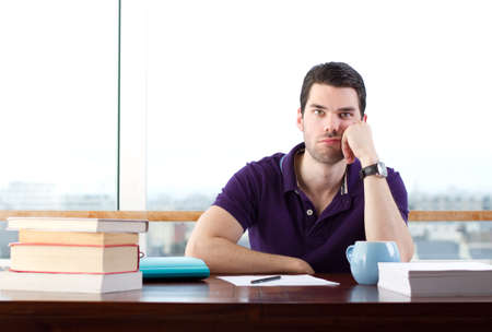 stuck up: Young man bored of studying, looks a little sad