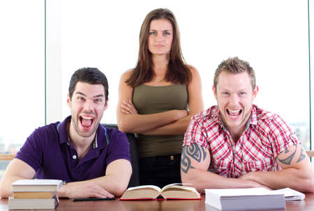 Two male students share a joke, the woman doesn't approve Stock Photo - 12040164