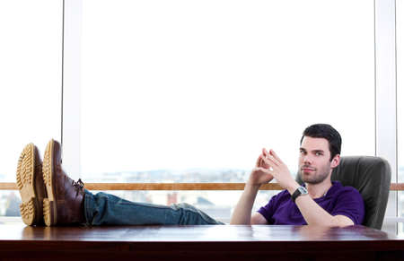 Young trendy man with his feet on a desk photo