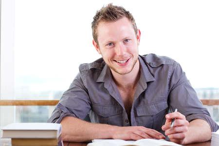 hombre escribiendo: joven estudiante estudiar duro en la biblioteca Foto de archivo