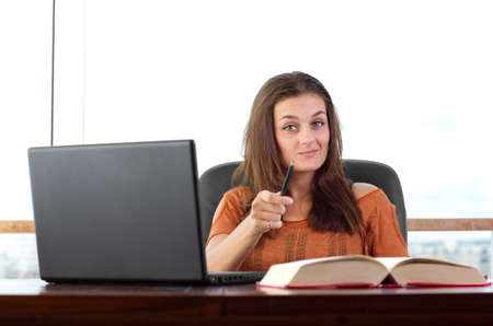 smug: Attractive young student happily studying and looking at the camera Stock Photo